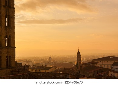 View of Arezzo historic center sunset skyline with old towers and churchs wrapped in mist