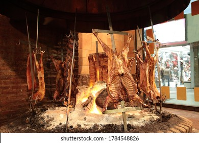 View of Argentine grilled meat Baby goat, Pork, Crosscut ribs and Rump steak on big flame of fire at a traditional Argentinean restaurant in Buenos Aires, Argentina