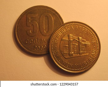 View of Argentinian coin. 50 centavos from Argentina. Great for numismatic collection. Shiny coin isolated on yellow surface of paper.