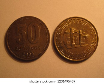 View of Argentinian coin. 50 centavos from Argentina. Great for numismatic collection. Shiny copper coin isolated on yellow surface of paper.