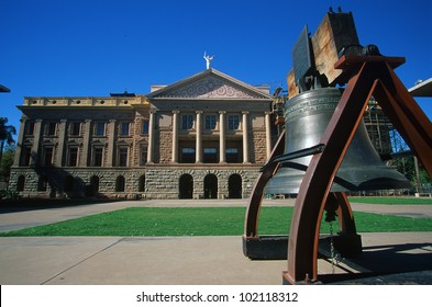 A view of the Arizona State Capitol with a bell in front.