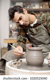 View at an artist makes clay pottery on a spin wheel in workshop