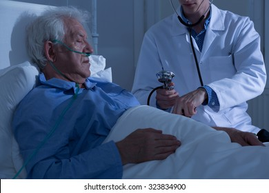 View of asleep old patient being examined by doctor