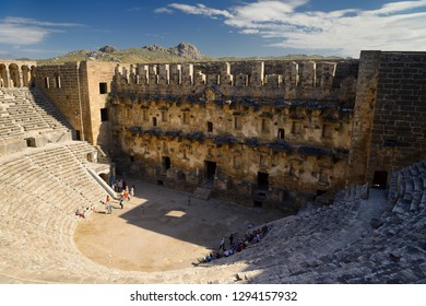 View of Aspendos theatre stage facade and distant hills from upper gallery with groups of tourists in Aspendos, Antalya, Turkey - November 8, 2012
