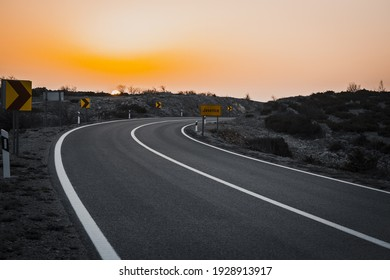 A view of an asphalt road with sunset scenery in the background