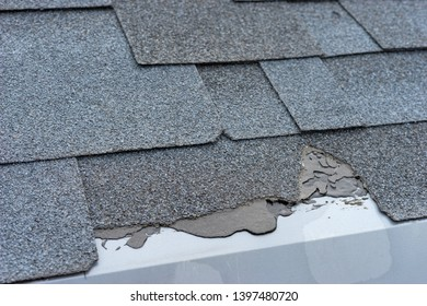 Сloseup view of asphalt shingles roof damage that needs repair.