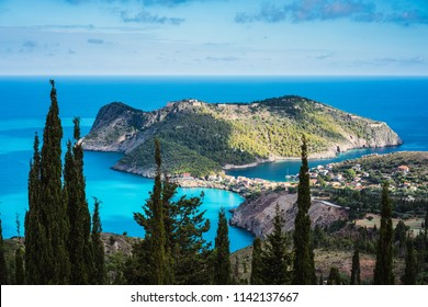 View to Assos village in sun light and beautiful blue sea. Cypress trees in foreground. Kefalonia island, Greece