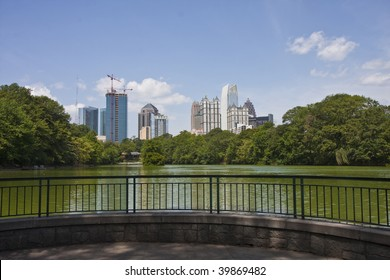 A view of the Atlanta Skyline shot from Piedmont Park with a small patio on the lake