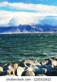 View of the Atlantic Ocean and the mountain covered with clouds from the embankment of Reykjavik on a sunny but windy day. Large stones divide the ocean and the embankment of the capital of Iceland