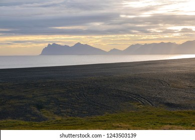View of the Atlantic Ocean and a volcanic black sand beach during sunset in the East Fjords, Iceland
