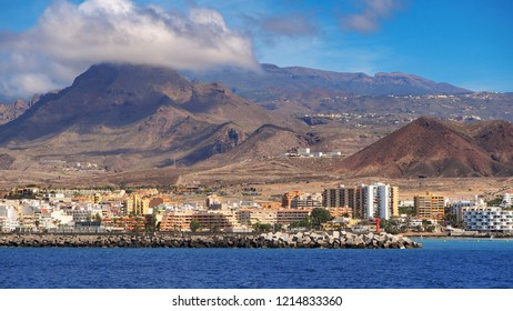 View from the Atlantic on the coast of Los Cristianos on Tenerife, a Canarian island. In the background several volcanic ash pits of the south-west coast, In front of it the colorful houses.