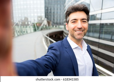 View of an Attractive middle aged business man taking selfie on the way to office - business concept