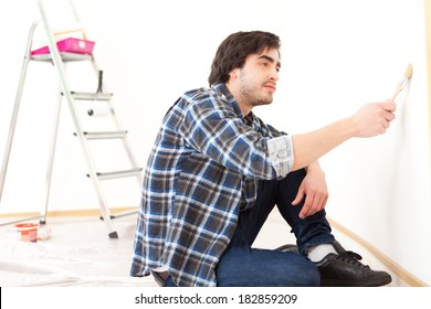View of an attractive young man painting a wall in his new flat