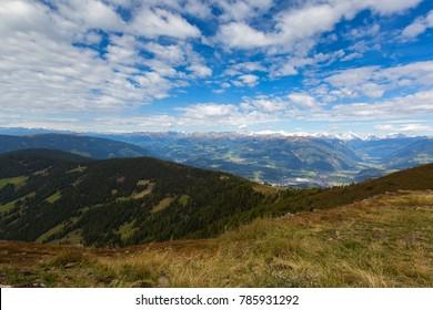 View of Austrian Alps mountain range, valley, snowy glacier mountains from afar, Autumn view from Mount Kronplatz, South Tyrol, Italy, Europe