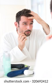 View of aYoung attractive man taking care of his hair