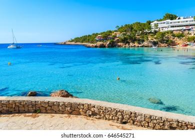 View of azure sea water in Cala Portinatx bay from coastal promenade, Ibiza island, Spain