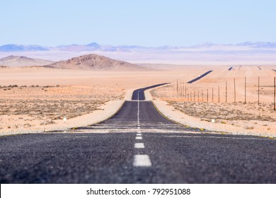 View of the B4 road between Lüderitz and Keetmanshoop near Garub in Namibia, Africa. The road cuts through the famous Namib Desert. Mountains in the background. Selective focus. Mirages in background.