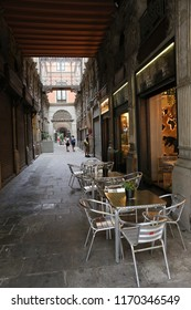 View of Bacardi passage, an ancient covered street leading to plaza real, in the Barri gothic district, central barcelona, Spain. August, 27, 2018. Narrow entrance with shops and a crossing bridge.