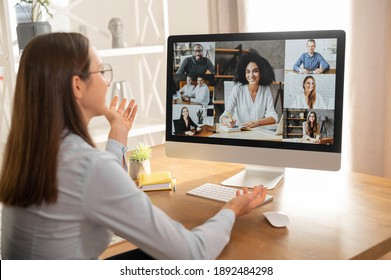 View from back above shoulder on the laptop with diverse employees, coworkers on the screen, video call, online meeting. App for video conference with many people together