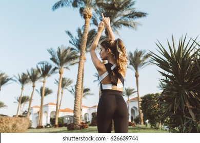 View from back amazing attractive woman in sportswear strecthing in tropical city. Sunny morning, palm trees, true emotions, healthy lifestyle, workout, fashionable model