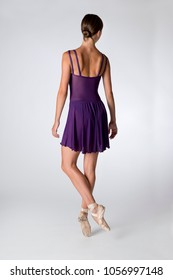 View of the back of a ballerina wearing purple leotards