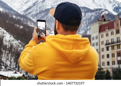 View from back. Bearded male tourist in yellow hoodie and cap stands on background of high snowy mountains and makes photos on smartphone. Traveler walks, takes photo in mountains. Lifestyle.