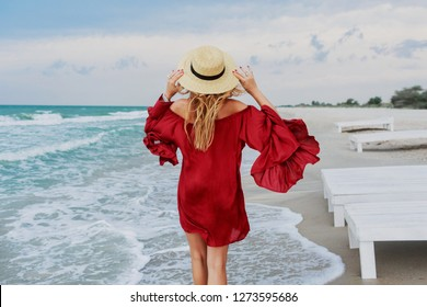 View from back of carefree graceful woman with amazing ginger hairs walking  along the beach . Summer mood. Traveling woman enjoins tropical vacations. Red dress. Straw hat.