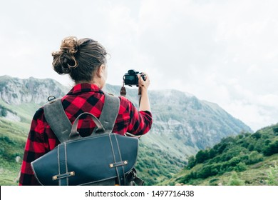 A view from the back of a female photographer, a blogger taking a photo of an epic mountain landscape. Adventure travel with backpack and camera.