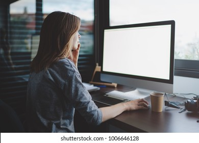view from back to female student is talking on smartphone sitting at desk in front of monitor with blank space for design. Mockup screen with copy space. woman makes a business call
