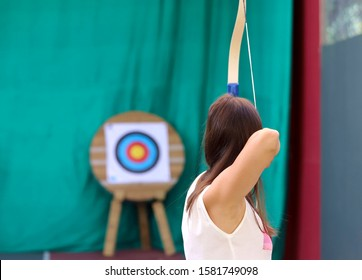 View from the back of a girl during archery. Cropped shot, horizontal, close-up. Sport and hobby concept.