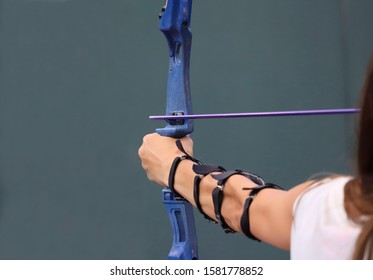 View from the back of a girl's hand during archery. Cropped shot, horizontal, close-up. Sport and hobby concept.