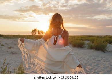 View from back of graceful ginger woman  enjoing amazing sunset on the beach. Boho style.