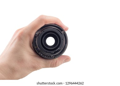 view of the back lens of the detachable camera lens in hand, the back of the lens, mount to the camera, isolated on white background