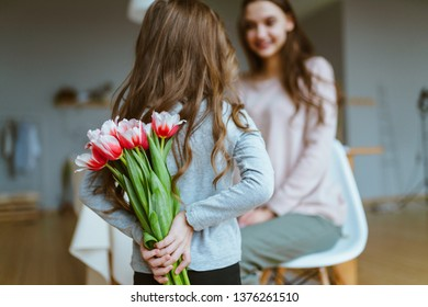 View from the back, a little girl holds a bouquet of tulips behind her back and gives her mother. Mothers Day
