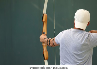 View from the back of a man during archery. Cropped shot, horizontal, close-up. Sport and hobby concept.