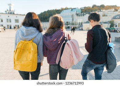 View from the back on three high school students. City background, golden hour.