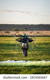 View from the back of the pilot running across the field with an individual knapsack parajet. Paralet with a gasoline engine. Flying on a motorized wing. Extreme sports. Paragliding and small aircraft