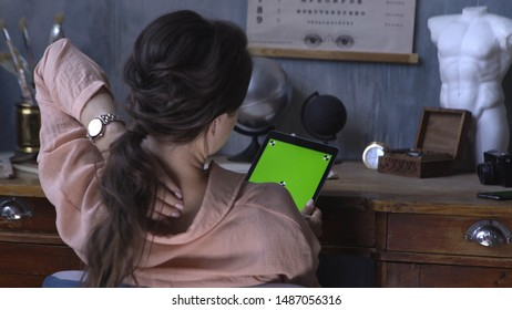 View from the back of pretty girl sitting at the table and using computer tablet with chroma key green screen. Stock footage. Chroma key screen for placement of your own content.