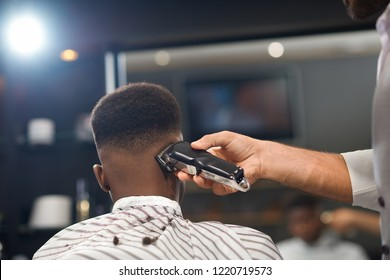 View from back of process of trimming hair of male client in barber shop. Barber keeping clipper in hand and shaving hair to man sitting on chair. Concept of stylish hairdressing and shaving.
