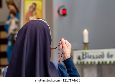 View from back of a religious sister holding rosary and praying at the altar.