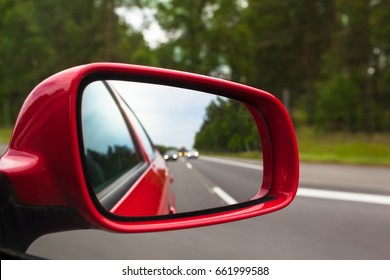 View back to road through red side mirror at car/Highway Rear View