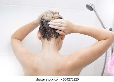 View from back of sexy young woman washing hair with shampoo at shower