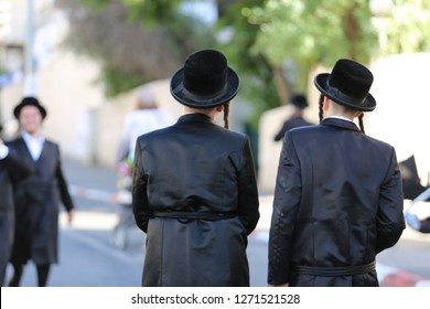 View from the back side of two ultra orthodox hasidic Jewish men wearing their traditional garb consisting of a long silk coat, fur hat, and side curls