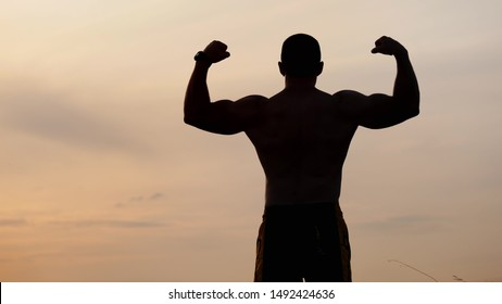 View from the back of silhouette of athletic man with a bare torso posing shows his muscles and biceps against the sky at sunset. Sport, health and fitness concept