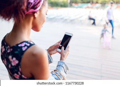 View from back of stylish mix race girl. Lifestyle image of black woman chatting by smartphone while relax in autumn park.