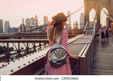 View from back of  traveling woman in red dress, stylish black  hat and silver bag pack enjoying amazing view from Brooklyn bridge in New York. Sunset colors.