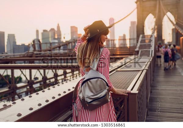 赤いドレスを着た旅行中の女性の背景から、スタイリッシュな黒い帽子と銀色のバッグパックを見て、ニューヨークのブルックリン・ブリッジから素晴らしい景色を楽しめます。夕焼けの色。