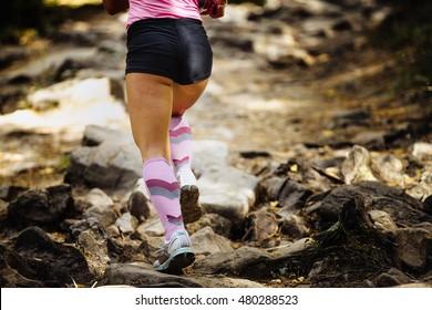 view of back woman marathon runner running mountain marathon on rocks, on feet compression socks