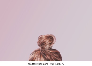 A view of the back of a woman's head. Hair wrapped in a bun on a light pink pastel background. Content completion concept.