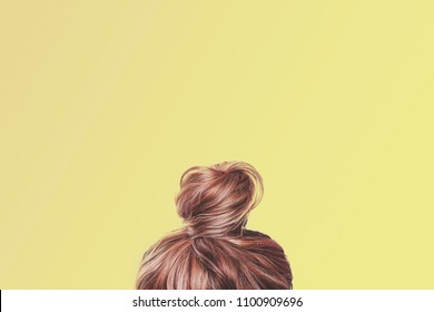 A view of the back of a woman's head. Hair wrapped in a bun on a light yellow pastel background. Content completion concept.